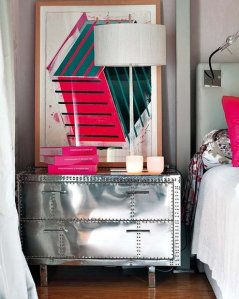 Industrial look: nightstand made of metal, styled with a big piece of art